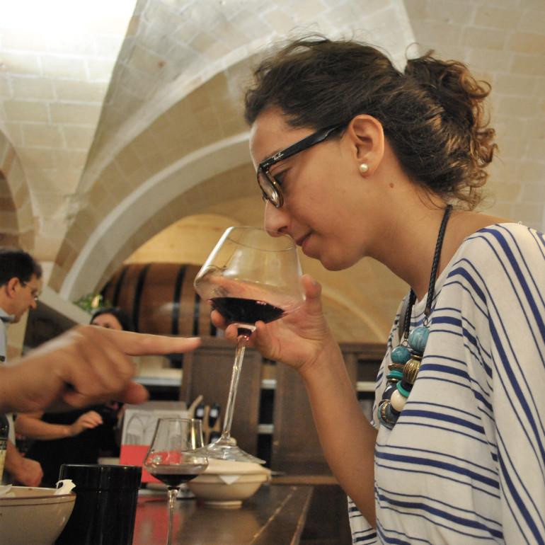 Lucia sniffs Primitivo di Manduria in Manduria. by Dauno Settantatre