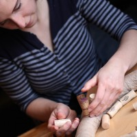 Madeline Puckette making a wine cork wreath