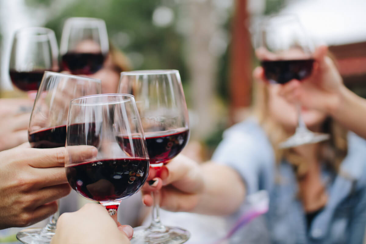 A group of people toasting with red wine. Photo by Kelsey Knight