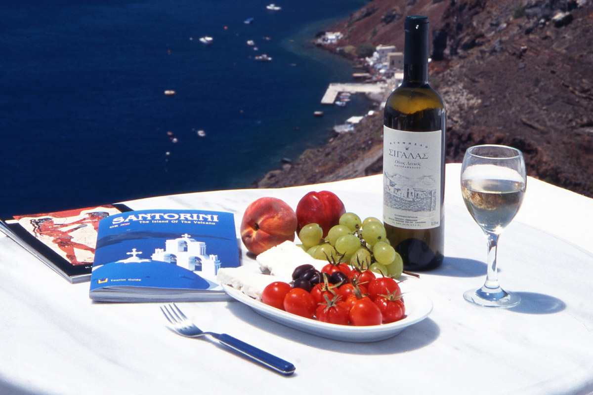 A view of Santorini, Greece with dinner and wine. Photo by Kamala Saraswathi