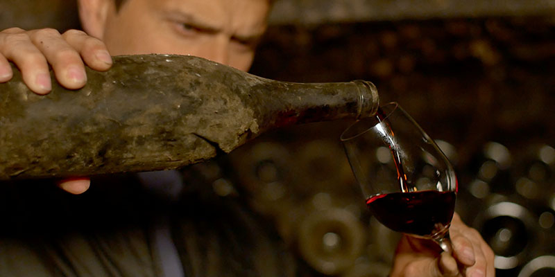 An old bottle of wine being poured in Somm Into The Bottle