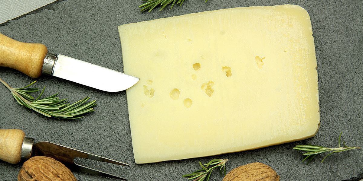 Fresh Asiago cheese on a cutting board.