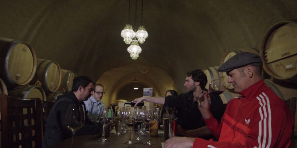 People tasting wines in a wine cellar in the movie Decanted.