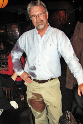 Man with red wine stains all over pants and shirt
