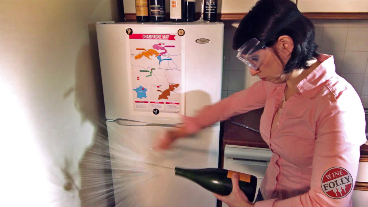 Madeline sabers Champagne with a spoon in the kitchen