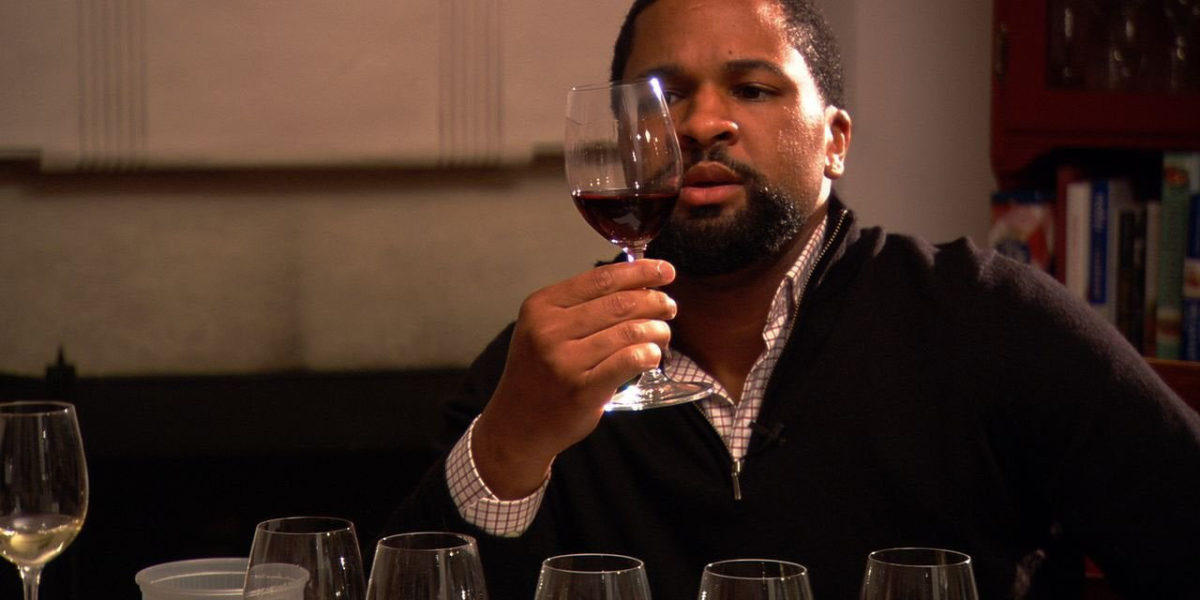 Dlynn studying a glass of wine in Somm movie