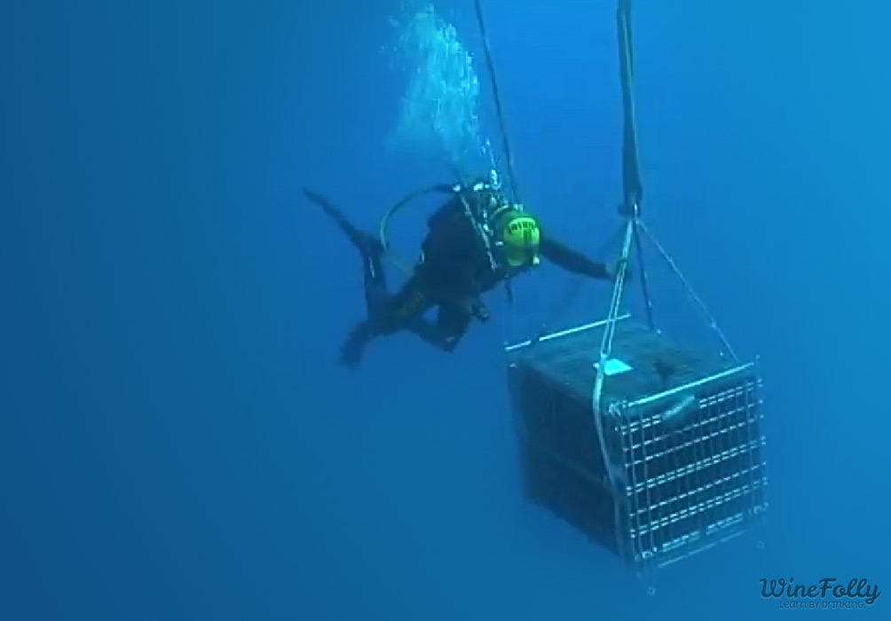 Man in scuba gear delivers the a wine treasure chest to its underwater resting place