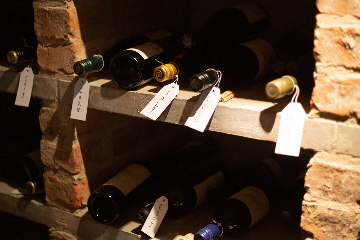 A wine cellar with labels on bottles.